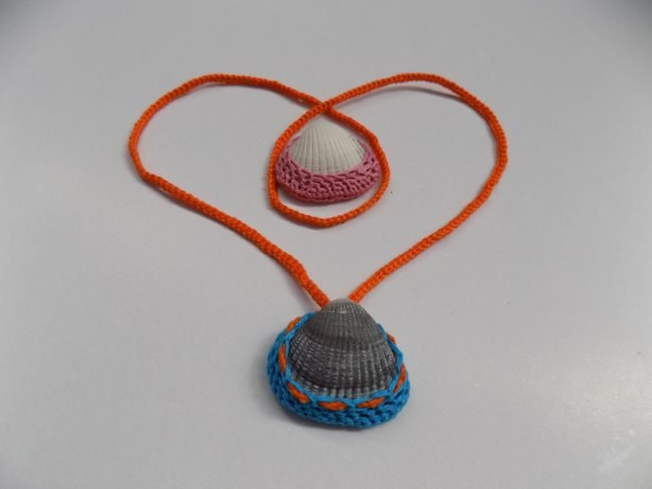 Pendant or necklace with a shell in a crochet frame